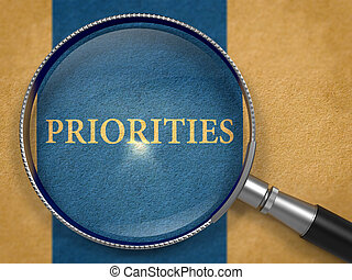 Priorities Concept through Magnifier on Old Paper with Dark Blue Vertical Line Background. 3D Render.