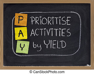 PAY (prioritise activities by yield ) acronym, principle of working smart, color sticky notes and white chalk handwriting on blackboard