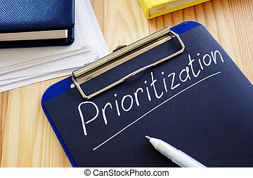 Prioritization handwritten sign on the black page.