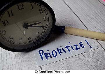 Prioritize! write on a book isolated on Office Desk.
