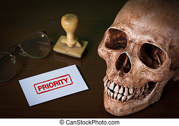 PRIORITY red rubber stamp and human skull