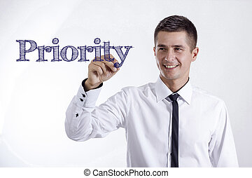 Priority - Young smiling businessman writing on transparent surface