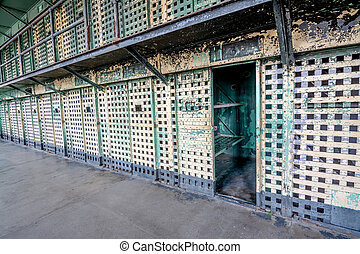 Prison cell block of barred doors and one is open