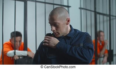 The jailer talks with a colleague on the walkie-talkie