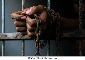prisoner - Prisoner with chain holding prison bar in jail