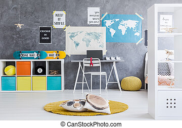 Boy room interior with maps, commode with skateboards on and desk