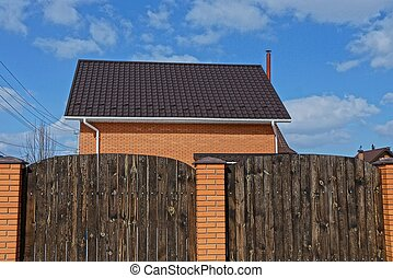 Private brick house with a tiled roof behind a brown wooden ...