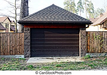 brown garage and part of the wooden fence in the street on the road