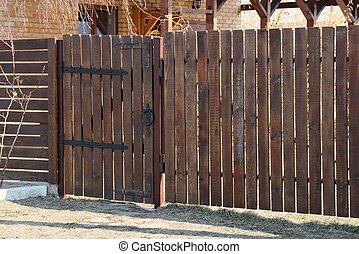 private brown gate and wooden fence of boards outside