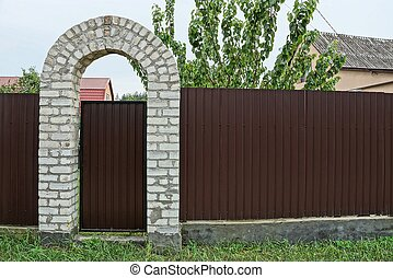 brown metal door and part of the fence in the street