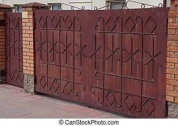 brown metal gate with forged pattern and brick fence in the street
