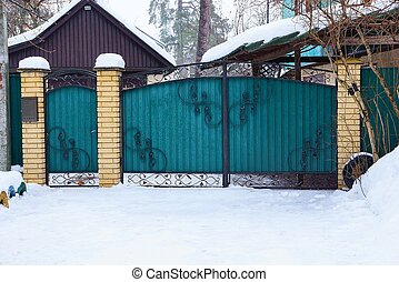 closed metal green gate with a black forged pattern on the street in white snow