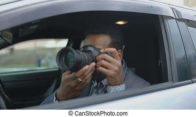 Private detective man sitting inside car and photographing...