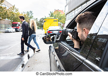 Private Detective Taking Photos Of Man And Woman