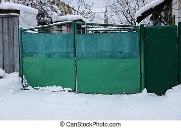 green metal closed gate and part of the fence on the street in white snow