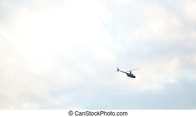 private helicopter flies a little in the gray clouds flying
