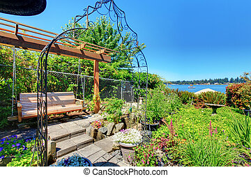 Private home Garden with a swinging bench near the lake.
