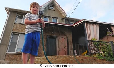 Private house in the summer. Small business concept. Boy in the backyard of a country house in the summer relax playing with water hose.