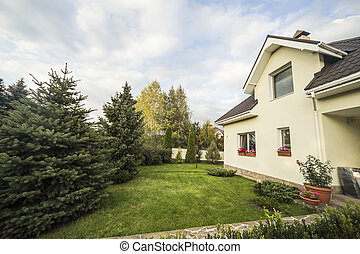Private house with a garden in a rural area under beautiful sky