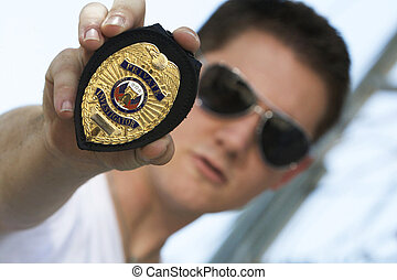 A male Private Investigator in sunglasses shows his badge aggresively.