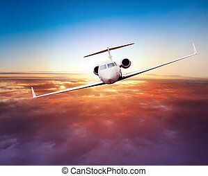 Private jet plane flying above clouds in beautiful sunset. ...