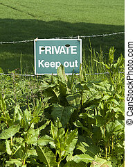 Private keep out sign on barbed wire boundary fence to ...