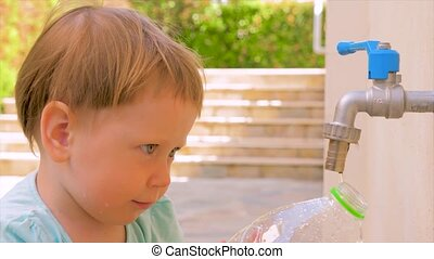 Private kindergarten background. Water problems on earth. Preschooler playing on backyard in the summer. Filling plastic bottle with water. Montessori concept. Lack of water. not enough fresh water
