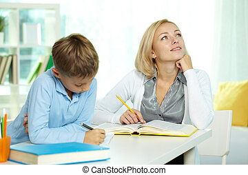 Portrait of diligent boy making notes at workplace with his thoughtful tutor sitting near by