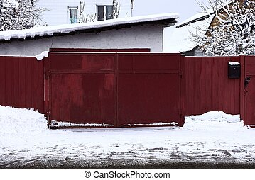 red metal closed gate and part of the fence on the street in white snow