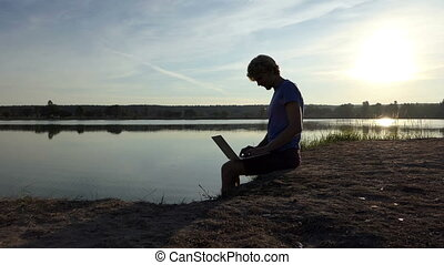 Pro man works with his laptop on a lake bank in slo-mo