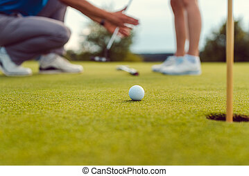 Pro on golf course teaching a woman how to put