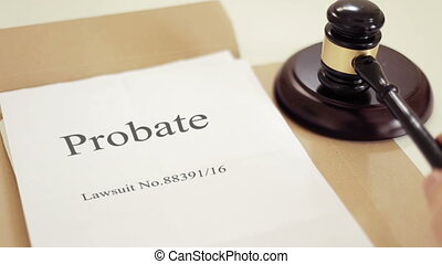 Probate lawsuit documents folder with gavel placed on desk of judge in court