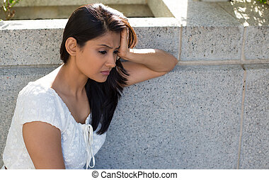 Closeup portrait, dull upset sad young woman in white dress sitting on bench, really depressed, down about something, isolated gray background. Negative emotion facial expression feeling body language