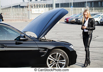 Problems on the road. Woman with broken car calling on smartphone