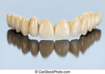 Beautiful porcelain teeth made by dental technician on mirror surface.