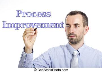 Process Improvement - Young businessman writing blue text on transparent surface