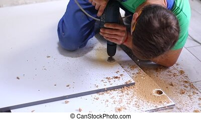 process of apartment renovation. drilling holes in furniture by fettler. sawdust scatter. unrecognizable men. remodeling, doing repairs