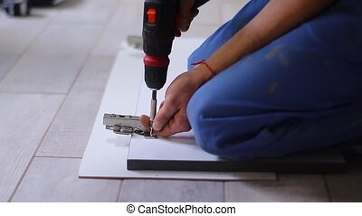 process of apartment renovation. fettler drills nails with a electric screwdriver into door hinges on the facade. unrecognizable men. remodeling, doing repairs. FullHD footage.