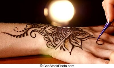 Process of applying mehndi on hand, back light, black -...