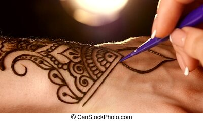 Process of applying mehndi on hand close up, back light, black