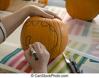Process of carving pumpkin to make Jack-o-lantern. Creating traditional decoration for Halloween and Thanksgiving. Woman drawing decor on big orange pumpkin
