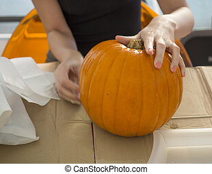 Process of carving pumpkin to make Jack-o-lantern. Creating traditional decoration for Halloween and Thanksgiving. Cutted orange pumpkin lay on table in woman hands.