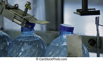 Process of closing plastic bottles with water in company....