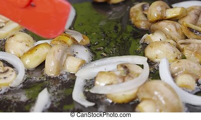 Process of cooking fried champignon mushrooms with onion in olive oil in a frying pan, close up. Stirring fried onion and champignons by red spatula. Macro shot. Beautiful wallpaper of cooking for restaurant. Slow motion.