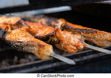 Process of cooking salmon skewers on grill - street food concept