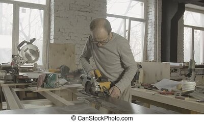 Process of cutting wooden board by professional carpenter. Woodworker. Furniture