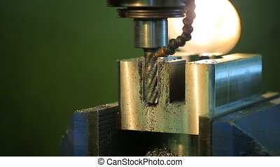 Process of deep drilling holes in metal clamped in vice of drilling machine tool.