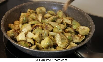 Cooking traditional Catalan vegetarian appetizer of roasted chopped young artichokes on frypan