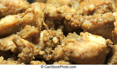 Process of frying chopped chicken pieces. Close-up