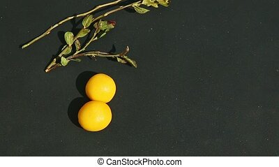 process of making one yellow double cherry shaped candy from two small pieces of marzipan mass on black table surface